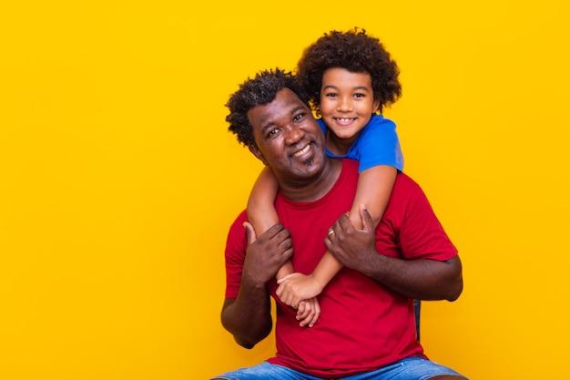 Vader en zoon op gele achtergrond. kinderdag- of vaderdagconcept