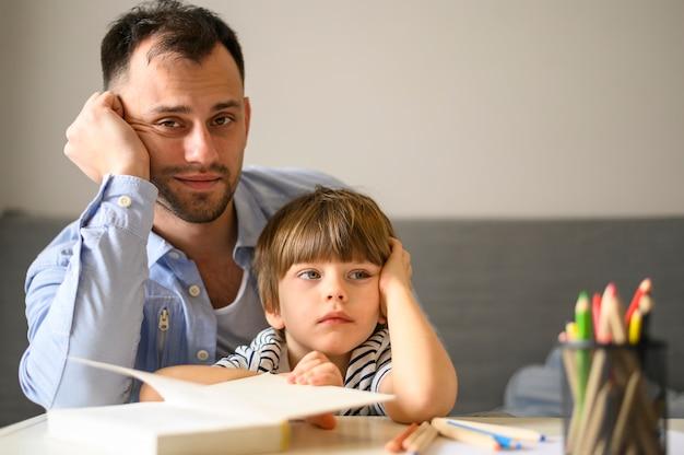 Vader en zoon poseren met boek