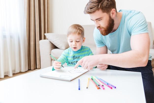 Vader en zoon praten en tekenen samen thuis