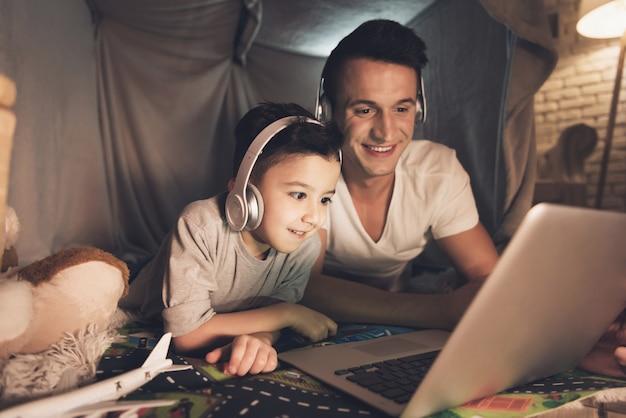 Vader en zoon praten op skype met familie op laptop