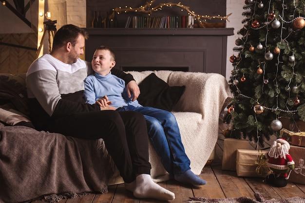 Vader en zoon praten thuis in de woonkamer bij de kerstboom.