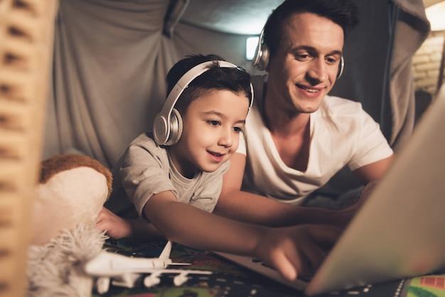 Vader en zoon praten via skype met familie op laptop.