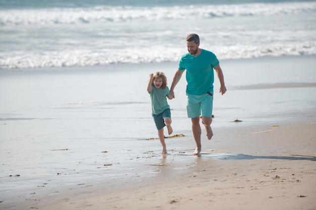 Vader en zoon rennen op zomerstrand, vader en kind hebben plezier buitenshuis
