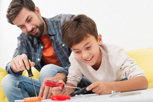 Vader en zoon repareren speelgoedauto's