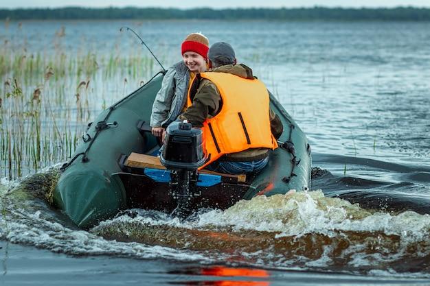 Vader en zoon rijden een motorboot op het meer.