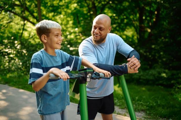 Vader en zoon rijden op scooters in het park