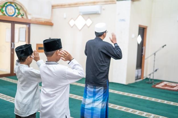Vader en zoon samen bidden in de moskee