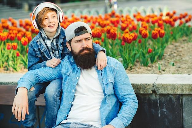 Vader en zoon samen wandelen. jonge vader met jongen die op een bank rust. familie, relatie en reisconcept.