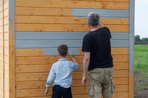 Vader en zoon schilderen een houten schuur met grijze verf op het perceel