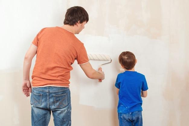 Vader en zoon schilderen een muur