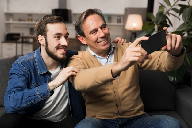 Vader en zoon selfie te nemen in de woonkamer