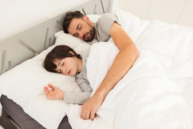 Vader en zoon slapen samen op het bed in hun huis.