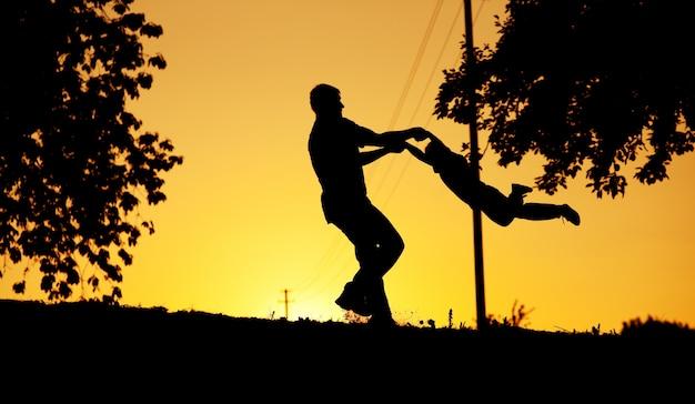 Vader en zoon spelen bij zonsondergang