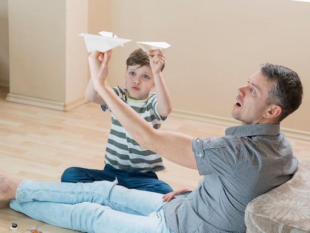 Vader en zoon spelen binnenshuis met papieren vliegtuigen