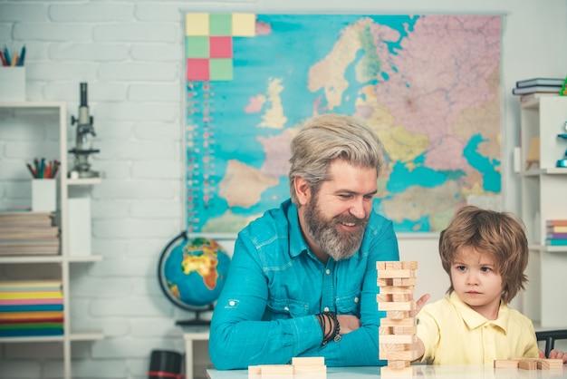 Vader en zoon spelen houten blokken stapelen jenga spelletjes huiswerk helpen schoolgemeenschap partnerschap