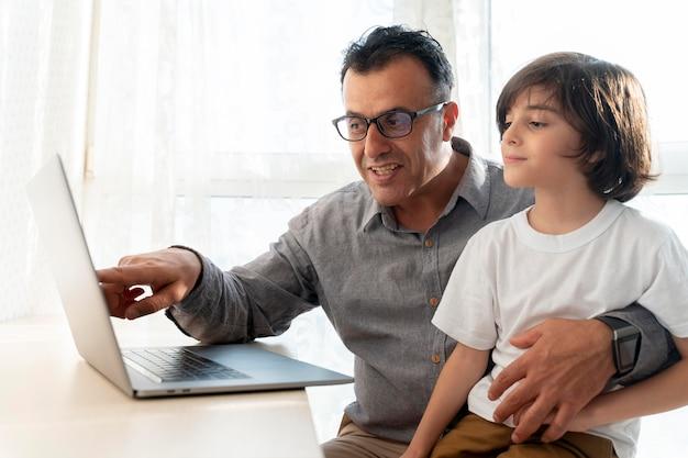 Vader en zoon spelen iets op een laptop