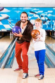 Vader en zoon spelen in bowlingcentrum