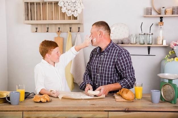 Vader en zoon spelen in de keuken