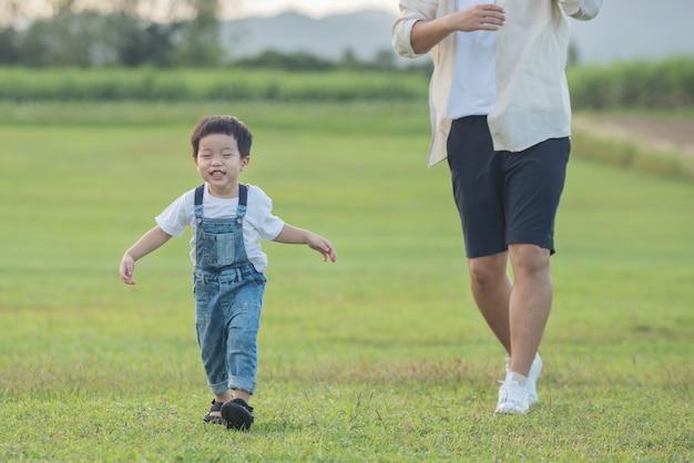 Vader en zoon spelen in het park bij zonsondergang. mensen die plezier hebben op het veld. concept van vriendelijke familie en zomervakantie. vader en zoon benen lopen over het grasveld in het park