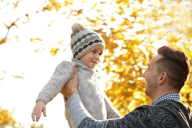 Vader en zoon spelen in prachtige herfst park