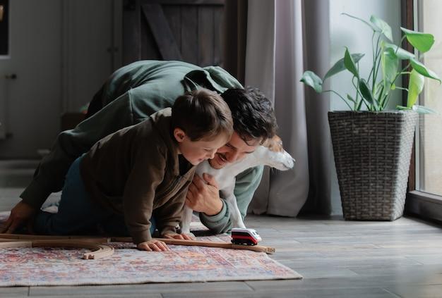 Vader en zoon spelen in treinen op een vloer thuis
