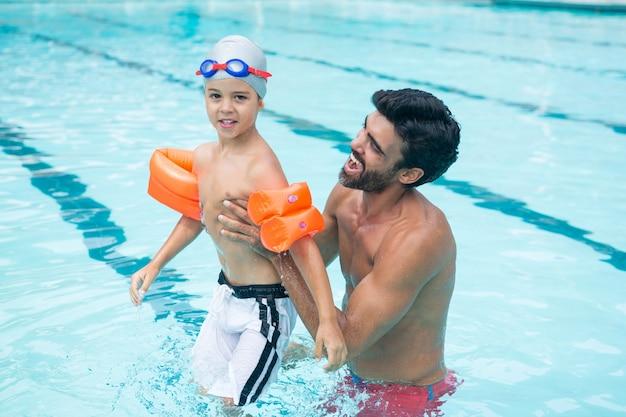 Vader en zoon spelen in zwembad