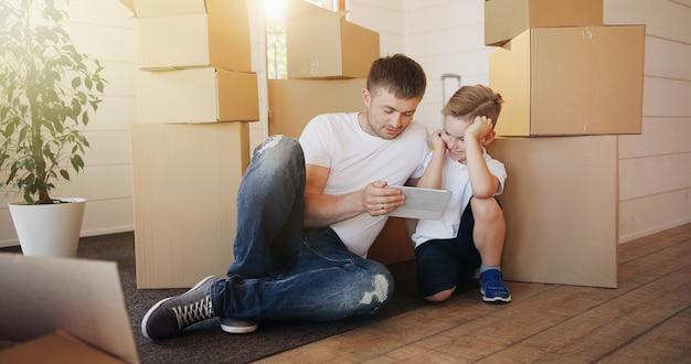 Vader en zoon spelen met digitale tablet omringd door dozen