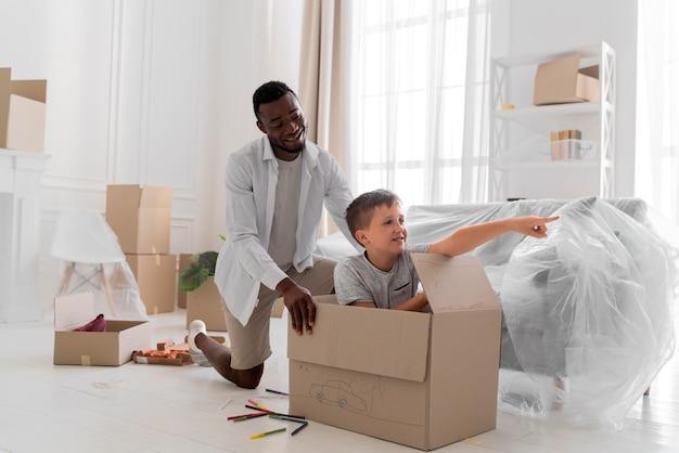 Vader en zoon spelen met een doos tijdens het verhuizen