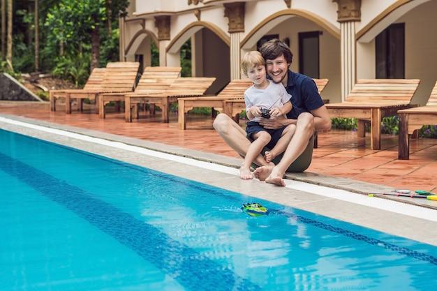 Vader en zoon spelen met een op afstand bestuurbare boot in het zwembad