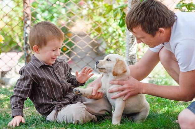 Vader en zoon spelen met een puppy labrador