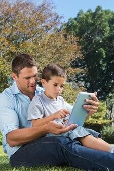 Vader en zoon spelen met een tablet-pc in een park