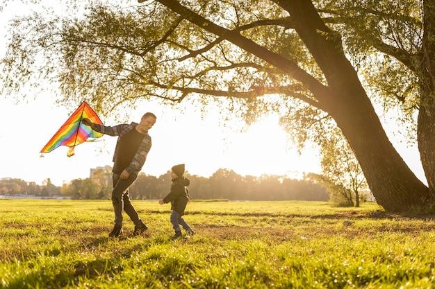 Vader en zoon spelen met een vlieger in park