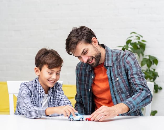 Vader en zoon spelen met speelgoedauto's