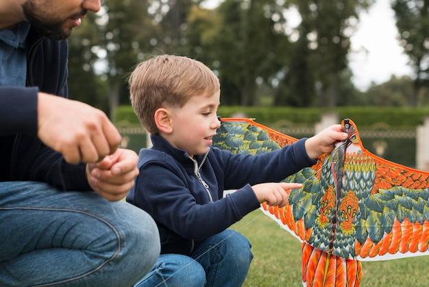 Vader en zoon spelen met vlieger in het park