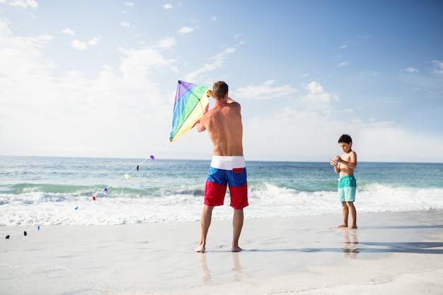 Vader en zoon spelen met vlieger