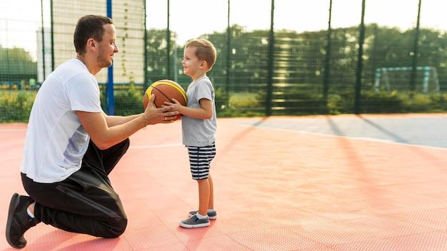 Vader en zoon spelen op de lange weergave van het basketbalveld