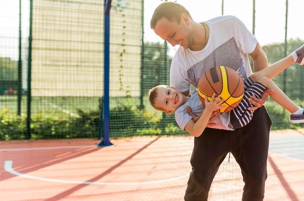Vader en zoon spelen op het basketbalveld