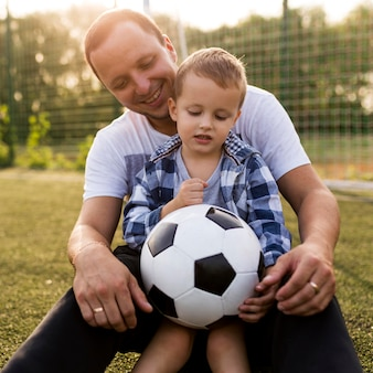 Vader en zoon spelen op het voetbalveld