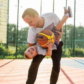 Vader en zoon spelen op het vooraanzicht van het basketbalveld