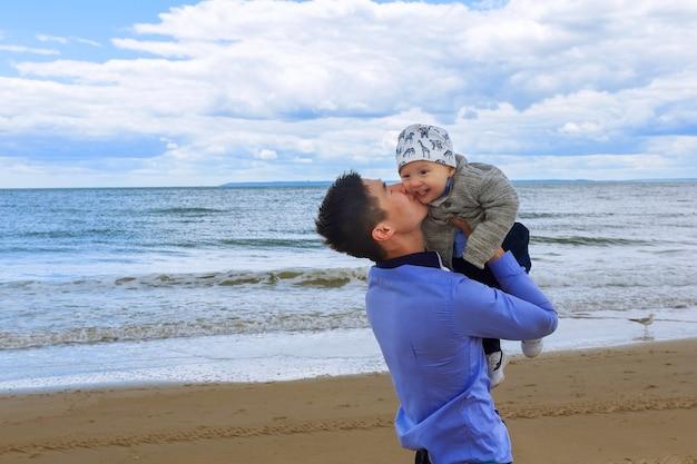 Vader en zoon spelen overdag op het strand. concept van vriendelijke familie.