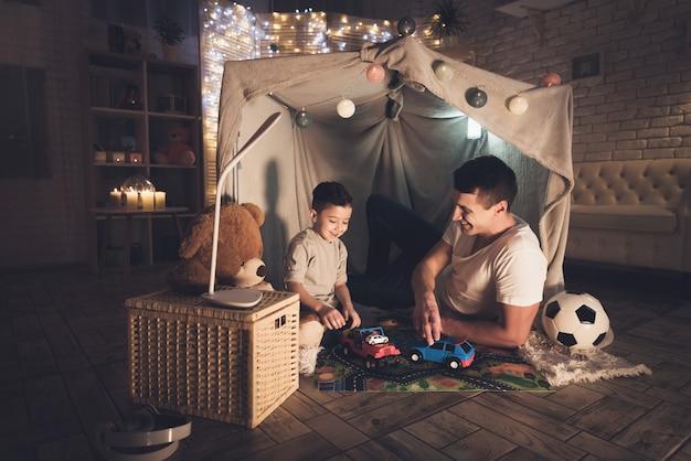 Vader en zoon spelen 's nachts thuis met speelgoedauto's.