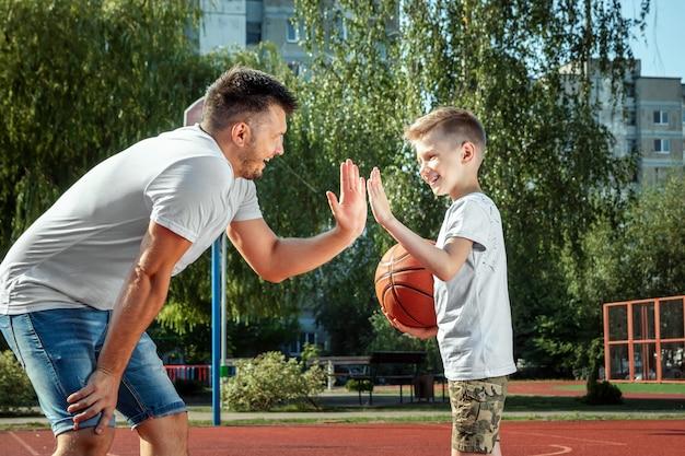 Vader en zoon spelen samen basketbal op het basketbalveld