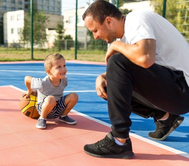 Vader en zoon spelen samen op het basketbalveld