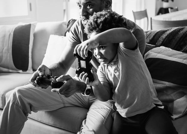Vader en zoon spelen samen spel in de woonkamer