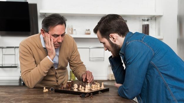 Vader en zoon spelen schaak in kithcen