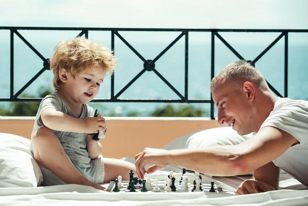 Vader en zoon spelen schaakman die jongen de regels van het schaak leert