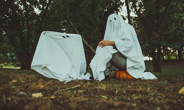 Vader en zoon spelen spoken met witte bladen in de tuin, conceptuele foto's over halloween