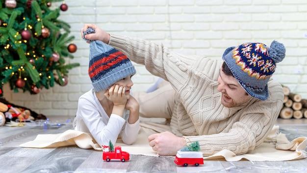 Vader en zoon spelen thuis op de vloer bij de kerstboom. gelukkig familie-idee