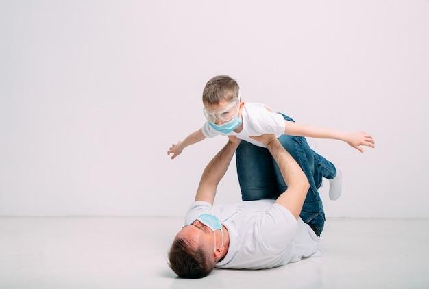 Vader en zoon spelen tijdens quarantaine in medische maskers.
