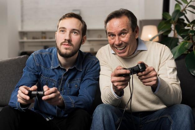 Vader en zoon spelen van videogames in woonkamer